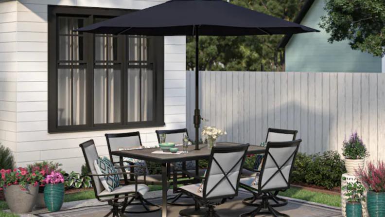 A set of black patio furniture sits in a suburban backyard.