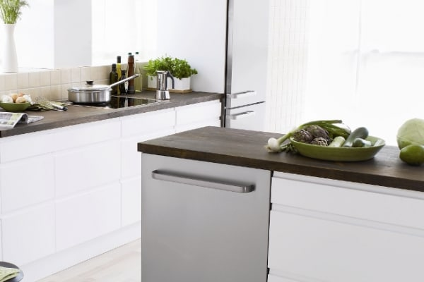 A fully integrated stainless steel Asko dishwasher set in the island of a traditional kitchen floor plan,