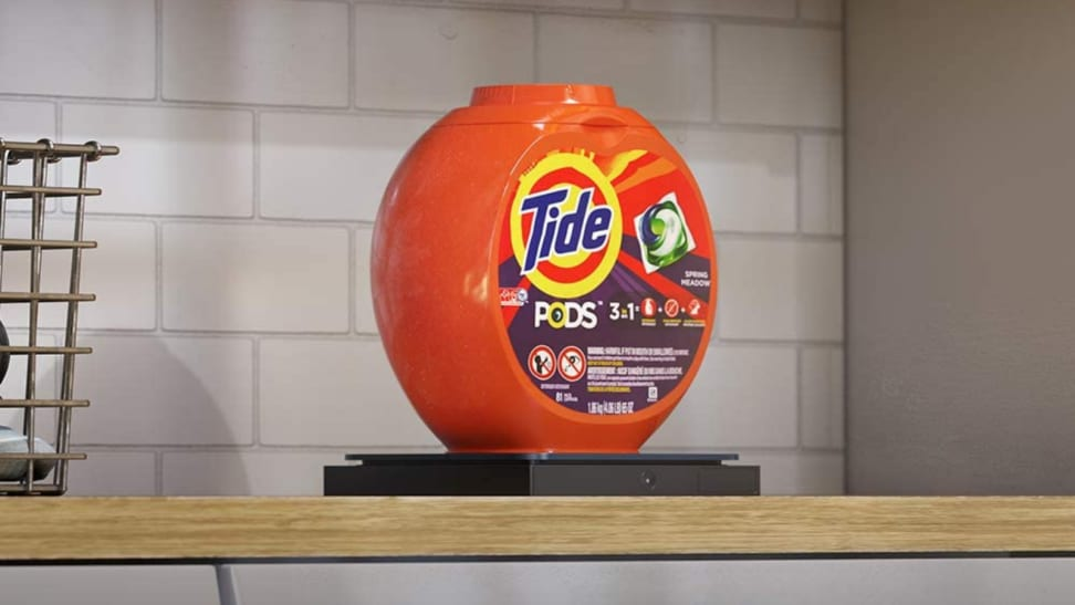 In a laundry room, a container of Tide laundry detergent is sitting on an Amazon Dash Smart Shelf.