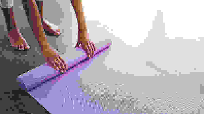 A person rolling up their yoga mat.