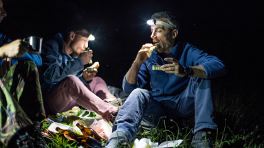 Campers eating and wearing headlamps.