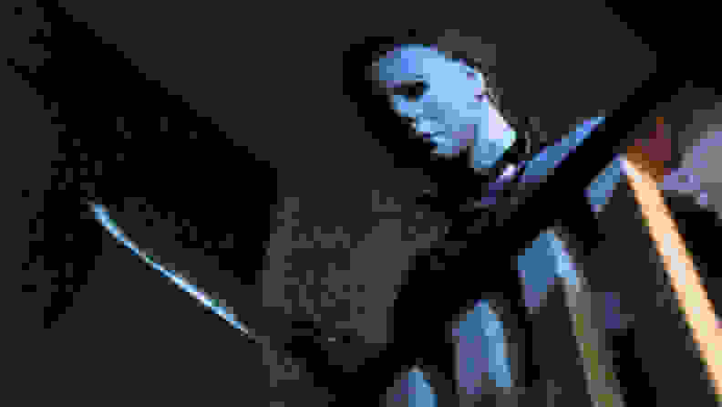 Michael Myers with a butcher knife leering over a staircase railing.