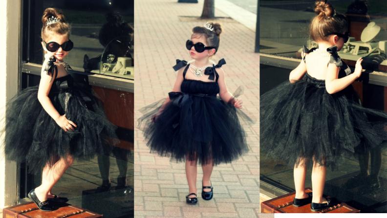 Child dressed up in Audrey Hepburn Halloween costume outdoors.