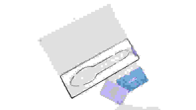 A white travel iron rests in blue packaging