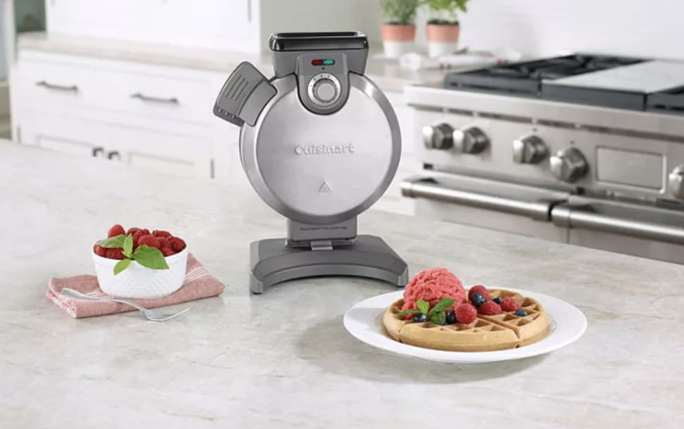 A vertical, Cuisinart waffle maker, sitting on a countertop next to a freshly made waffle with strawberry topping.
