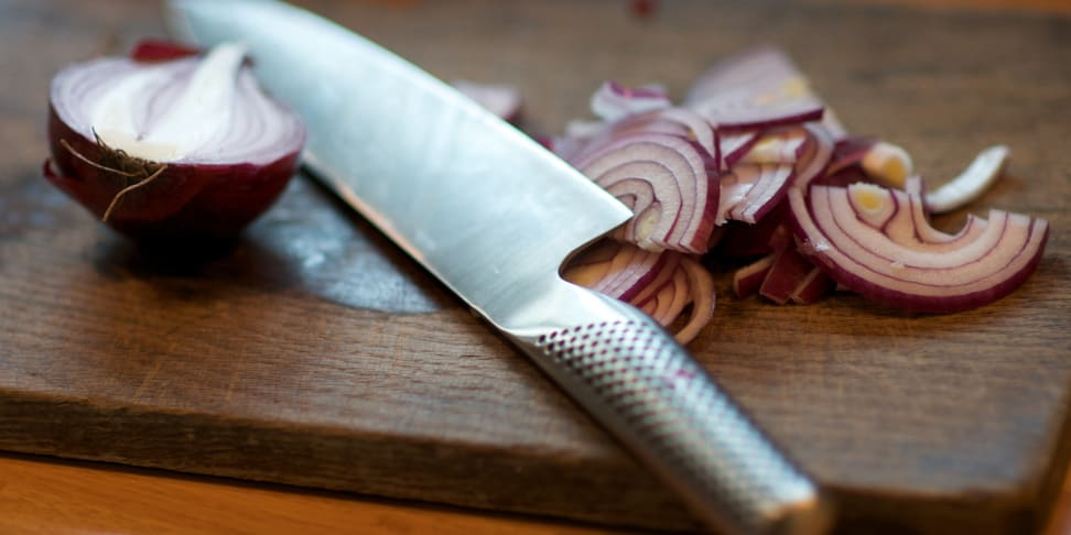 knife on cutting board with onions