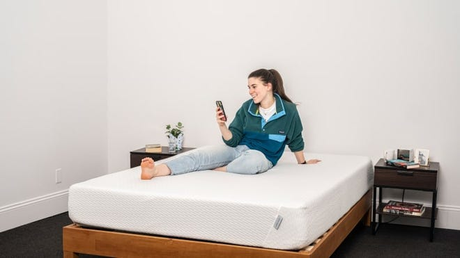 Person reclining on mattress while smiling at smartphone.