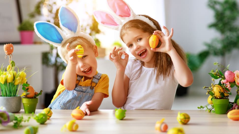 Brother and sister wearing bunny ears playfully hold up colored Easter eggs