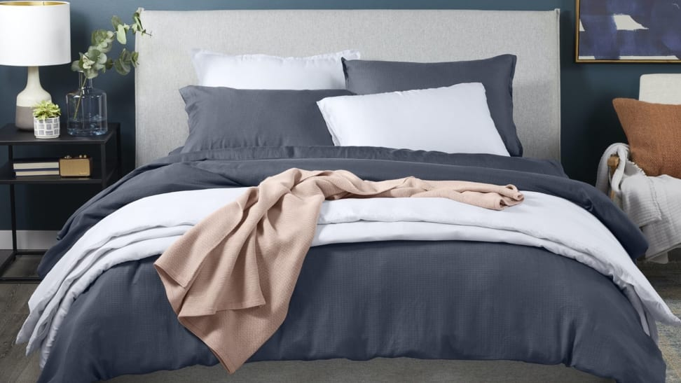 The Casper hyperlite sheets in a dark gray on a made bed