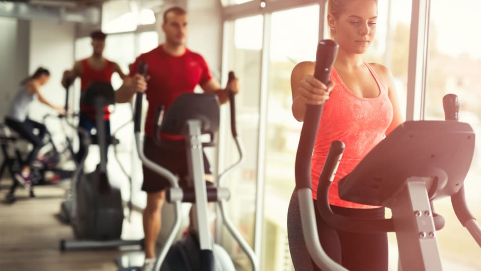 A woman and a man using elliptical machines at the gym.