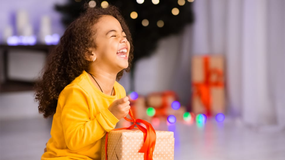 A young girl holds a wrapped present and laughs