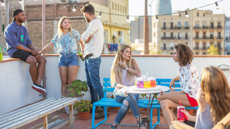 A group of friends gather on a rooftop terrace.