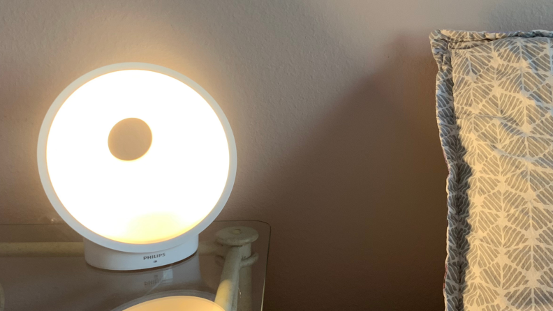 Image of the Philips Connected sunrise alarm at full brightness in a room on a clear end table next a bed with a grey pillow