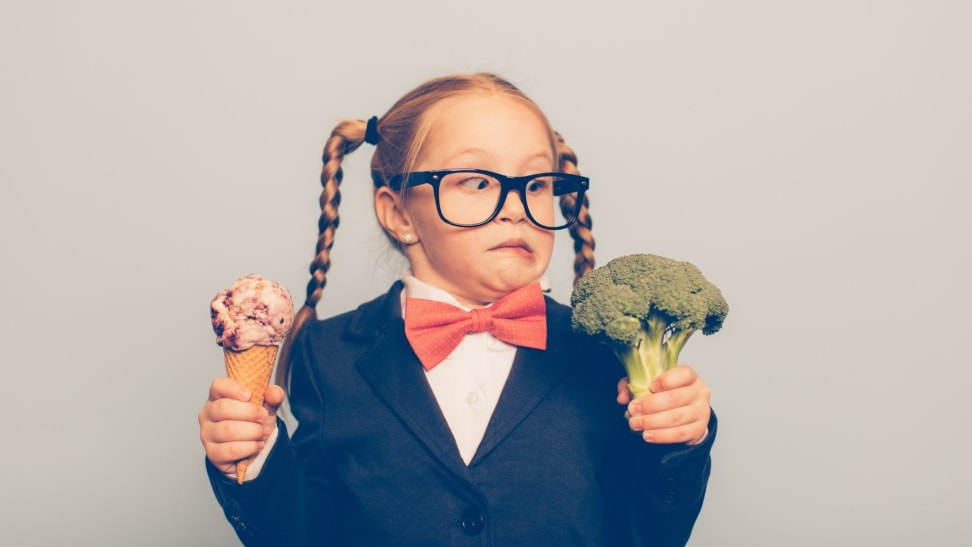 Little girl holds ice cream in one hand, broccoli in the other hand, making a silly face at the broccoli.