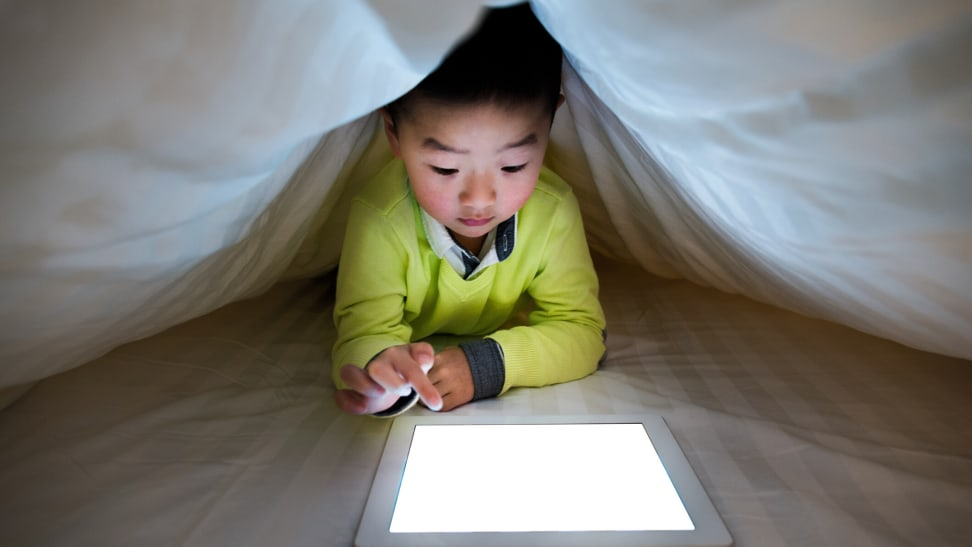 Kid on tablet under the covers