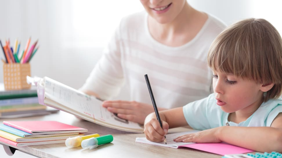Parent and child working together over books at table