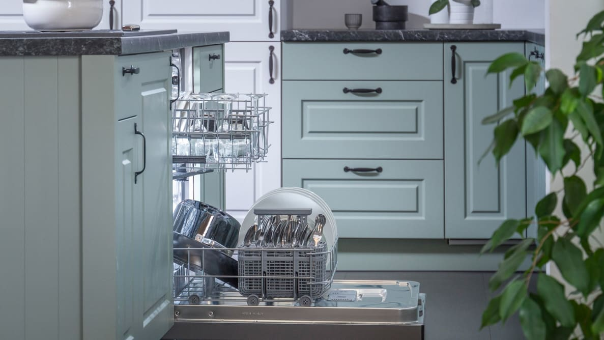Hisense HUI6220XCUS dishwasher review—Pictured is a shot of the Hisense HUI6220XCUS dishwasher installed into a typical kitchen, from a side angle. Its door is open and its racks have been pulled out slightly. Both racks are stocked with dishes.