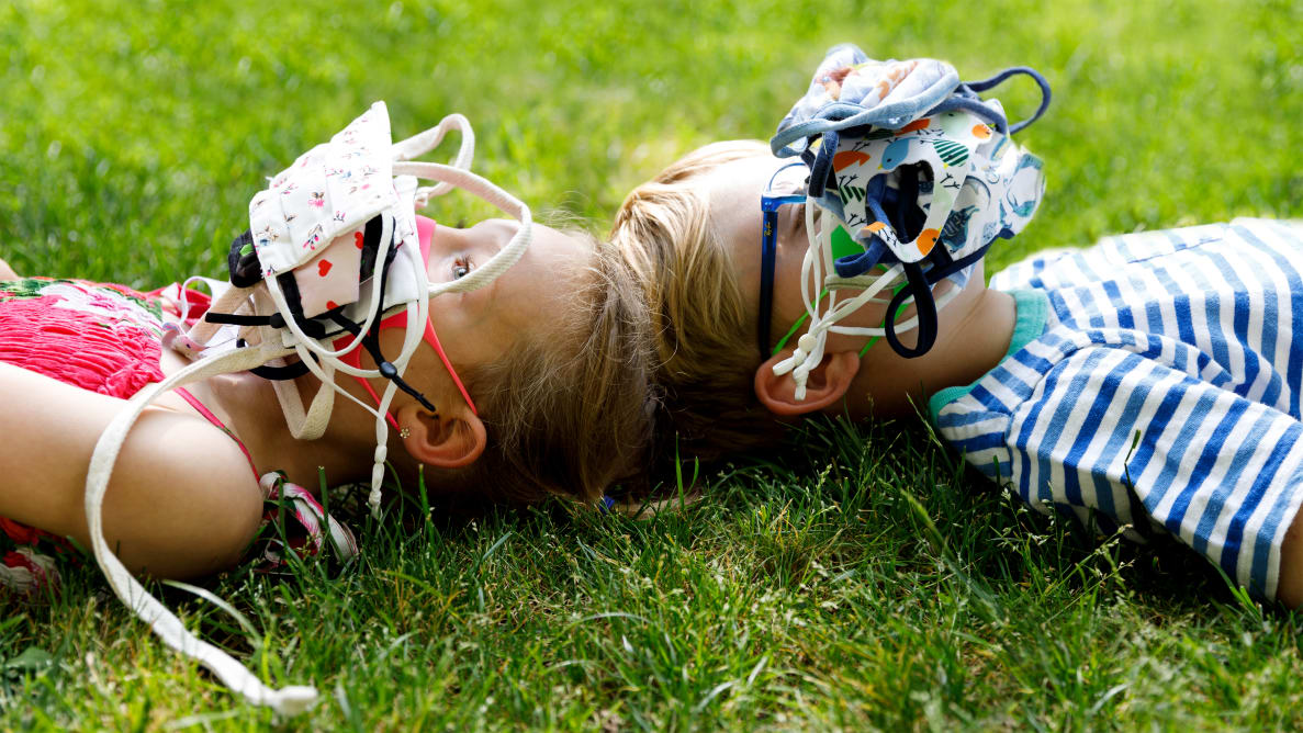 Two young children laying on the grass with their faces covered in a piles of face masks