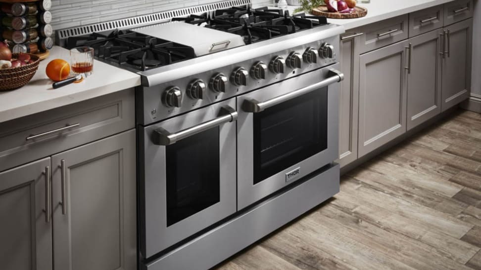 A stainless steel, professional-grade double oven range is brightly lit in a modern looking kitchen.