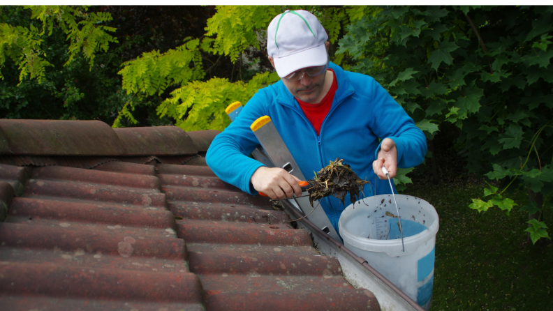 Man on a ladder cleaning gutter on the roof with a trowel and bucket