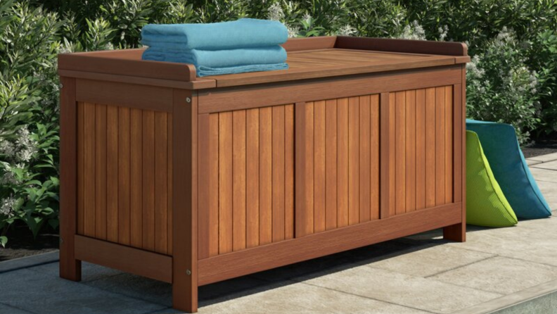 Wooden deck box on a patio with blue towels on top