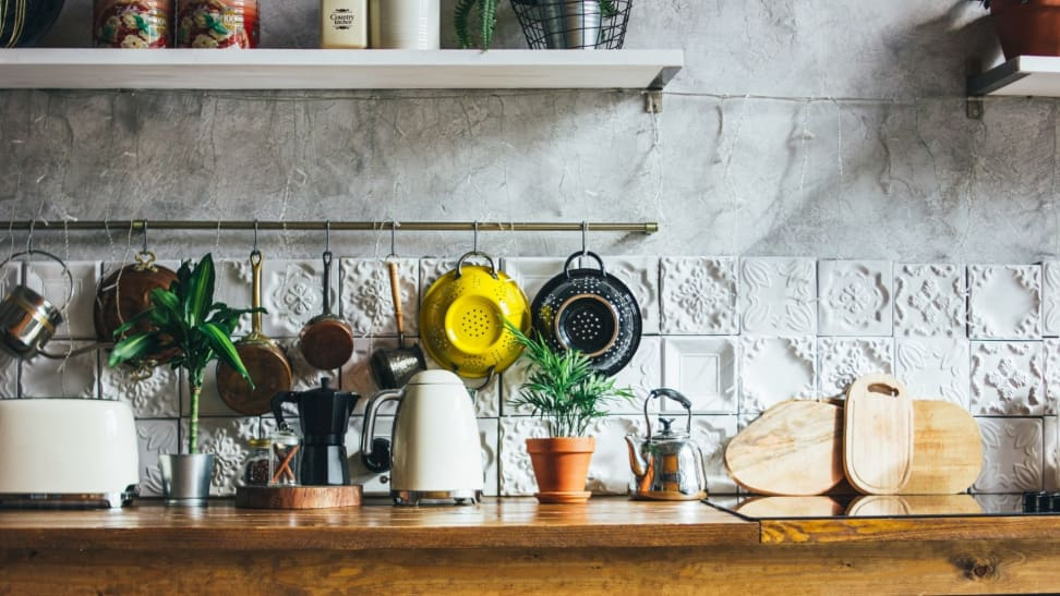 A sunlit kitchen counter filled with plants and small appliances including a black moka pot, wooden cutting boards, a white two-slice toaster, a white electric kettle, and two colanders hanging above them on the textured white wall.