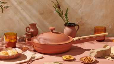 The terracotta-colored Always Pan is in the center of the image. The color is earthy with an orange hue. Next to the pan, pottery vases, drinkware, and plates of nuts and snacks are on display..