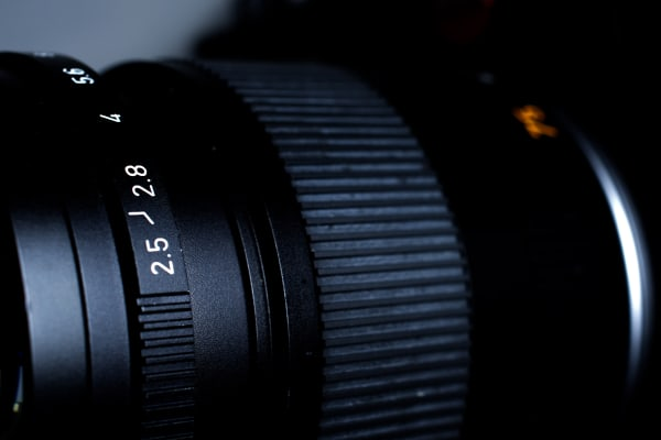 the 75mm f/2.5 lens is very well built, with focus distance markings and a physical aperture dial on front.