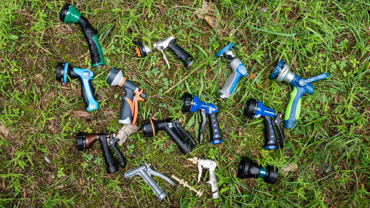 14 hose nozzles lay scattered on wet grass