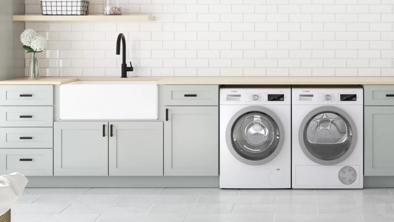 Matching washer and dryer in modern laundry room.
