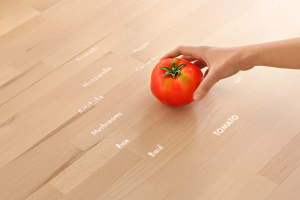 Cameras, sensors, and projectors combine to create a smart surface that reacts to what you put on it. Induction technology even lets you use it as a safe cooking surface.
