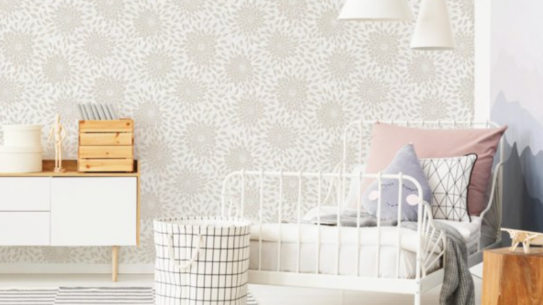 A beige floral design wallpaper in a room with a white dresser on the left and a white twin-sized bedroom on the right.