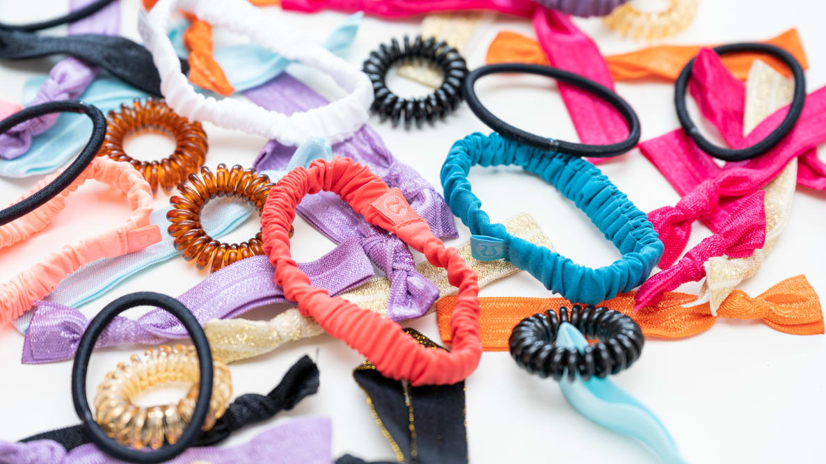 A smattering of colorful hair ties sprawled across a white surface.