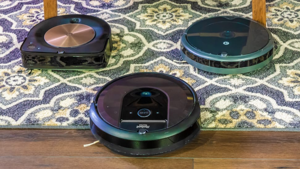 A group of three iRobot Roomba models on the capret