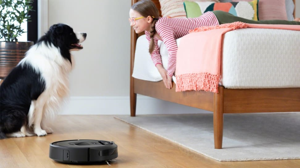 Dog and girl looking at each other with a robot vacuum on the floor