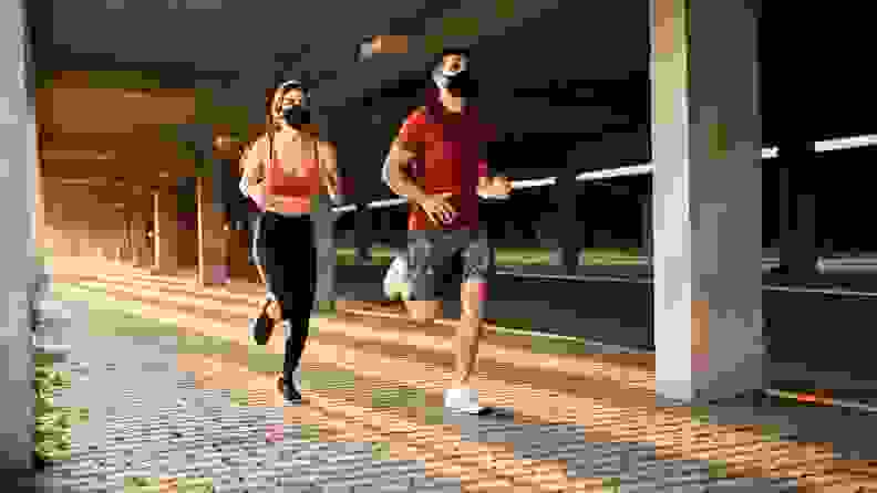 couple running wearing masks