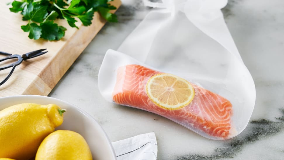 On a marble kitchen counter, a piece of salmon fillet and a slice of lemon are in an Anova silicone sous vide bag. Next to the bag, two lemons and some fresh herbs are scattered around.