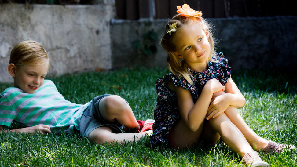 Two children sit on the grass.