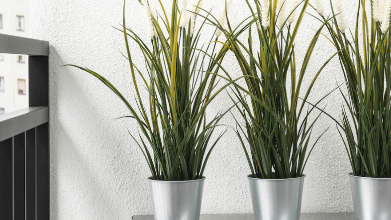 Faux grass plant in metal tins on table.