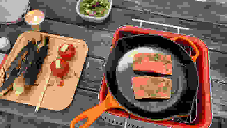 An orange cast iron skillet is placed on top of the Everdure Cube charcoal grill. In the skillet, there are two pieces of salmon. Next to the grill, there's a bamboo tray of cooked corn and tomatoes.