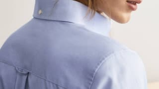 Woman wearing blue oxford button-down shirt with locker loop visible.