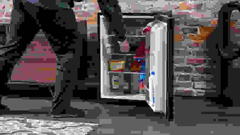 A person reaching into a black mini fridge.