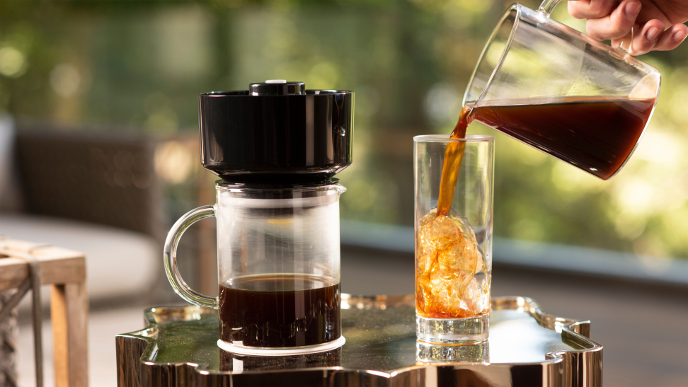 A VacOne Air Brewer coffee maker is in the center of the image. Right next to it, a person is pouring coffee into a glass half-filled with ice cubes.