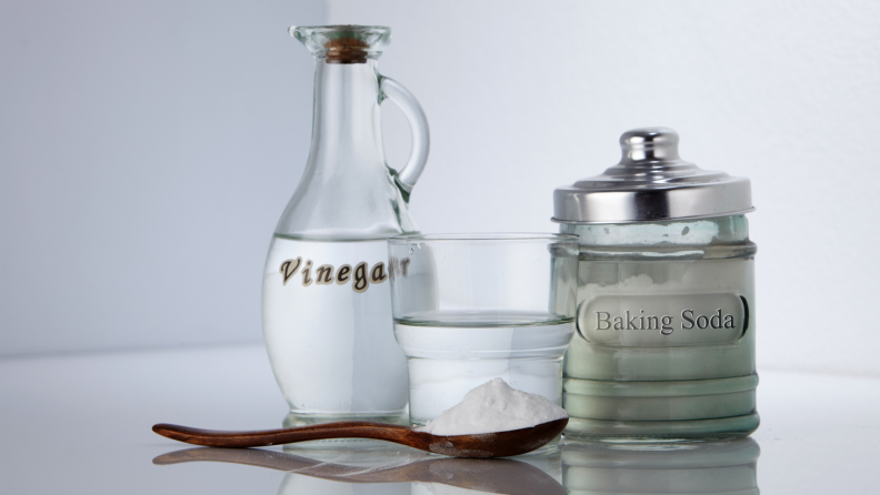 Containers of vinegar, baking soda, a glass of water, and a spoonful of baking soda.