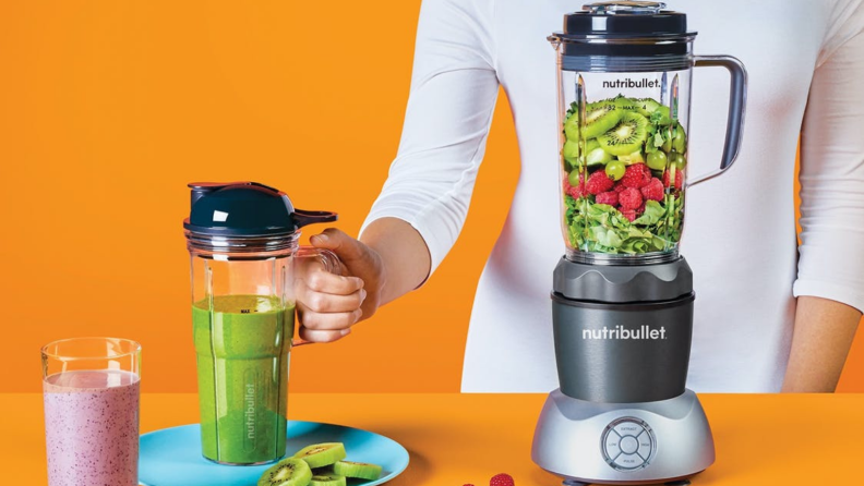 A person is making a smoothie using the NutriBullet Select blender.
