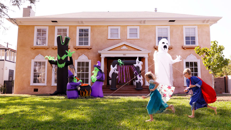 A house with 4 Halloween inflatables on the lawn and two children running