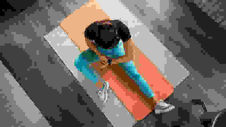 A woman checking her fitness tracker on a yoga mat.
