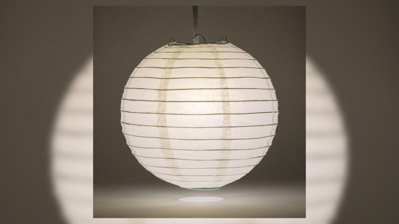A lit paper lantern in a dark room.