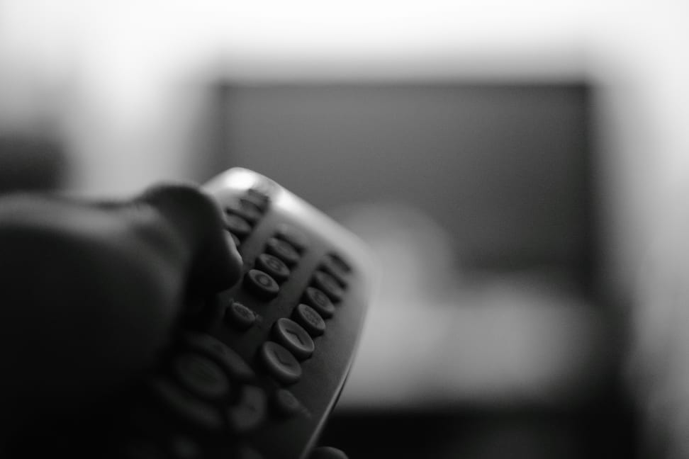 A person points a TV remote at a TV