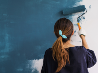 Woman painting a white wall blue with a paint roller